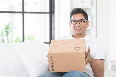 parcel: Courier delivery concept. Indian guy received an express parcel and checking the box at home. Asian man sitting on sofa indoor. Stock Photo
