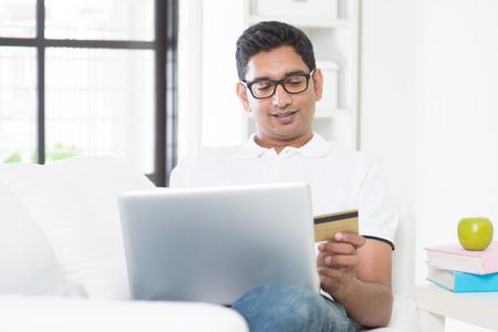 pagando: Chico indio de compras mano la tarjeta de crédito de retención en línea con el ordenador portátil en casa. Hombre asiático compra de internet, relajado y sentado en el sofá de interior. Modelo masculino hermoso.