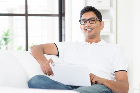 Portrait of Indian guy with digital tablet computer at home. Asian man using internet, relaxed and sitting on sofa indoor. Handsome male model.
