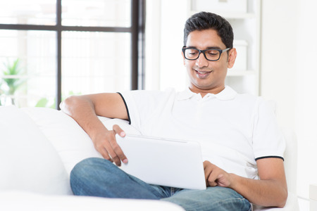 working at home: Portrait of Indian guy reading on digital tablet computer and smiling at home. Asian man using internet, relaxed and sitting on sofa indoor. Handsome male model. Stock Photo