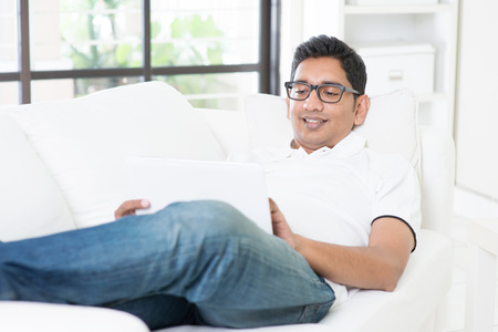 indian business man: Indian guy using digital computer tablet at home. Asian man relaxed and lying on sofa indoor. Handsome male model.