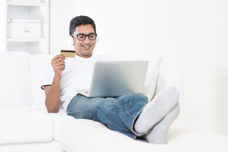 Indian guy making online credit card payment with laptop computer at home. Asian man internet shopping indoor  relaxed and sitting on sofa. Handsome male model.