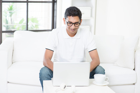 indian business man: Young Indian guy start his new business with laptop computer from home. Asian man using internet indoor, relaxed and sitting on sofa. Handsome male model working indoors. Stock Photo