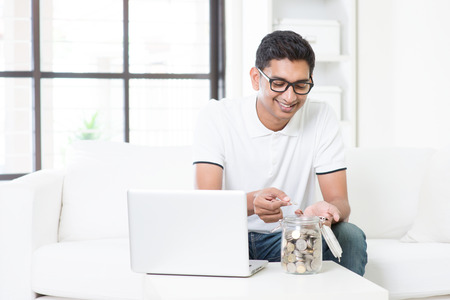 Indian guy using internet computer and counting coins at home. Asian man relaxed and sitting on sofa indoor. Stock Photo