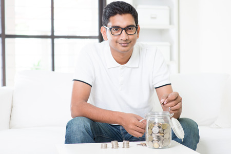 Investment concept. Indian guy saving money to glass jar. Asian man sitting on sofa indoor. Handsome male model.