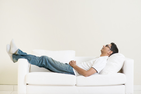 lying on couch: Indian guy daydreaming and rest at home. Asian man relaxed and sleep on sofa indoor. Handsome male model.