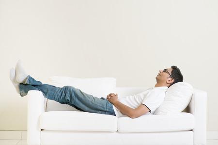 Soñar despierto chico indio y el descanso en casa. Hombre asiático relajado y dormir en el sofá de interior. Modelo masculino hermoso. Foto de archivo