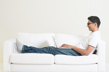relajado: Trabaje desde su concepto de hogar. Chico indio que usa el ordenador portátil. Hombre asiático relajado y sentado en el sofá de interior. Modelo masculino hermoso.