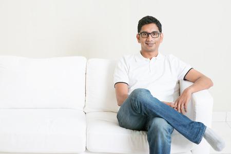 hombre sentado: Apuesto hombre joven indio que se sienta en el sof� y sonriendo. Hombre asi�tico Estilo de vida en el hogar. Modelo masculino hermoso. Foto de archivo