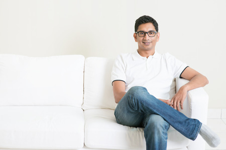 Good looking young Indian guy sitting on sofa and smiling. Lifestyle Asian man at home. Handsome male model.