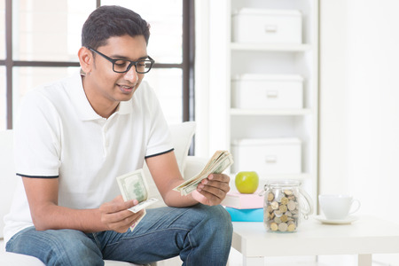 Indian guy counting money and smile at home. Asian man holding cash indoor. Imagens