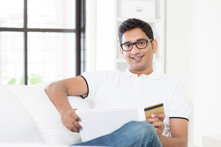 card making: Indian guy hand holding credit card, making internet online payment using digital computer tablet at home. Asian man relaxed and sitting on sofa indoor. Handsome male model. Stock Photo