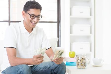 salarios: Chico indio feliz contando dinero y sonreír en casa. Hombre asiático celebración de efectivo feliz interior.