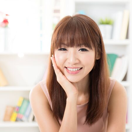 beautiful teeth: Portrait of Asian girl hand holding face, relaxed and smiling at home, woman living lifestyle indoors.