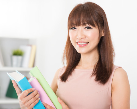 one room school house: Portrait of happy Asian college girl hands holding books. Young woman at school library.