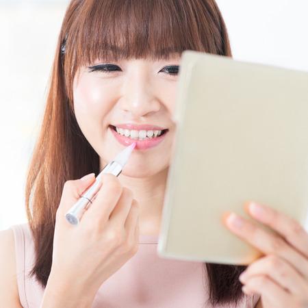 l�piz labial: Retrato de la atractiva chica asi�tica que pone el l�piz labial en los labios. El estilo de vida de estar Mujer joven.