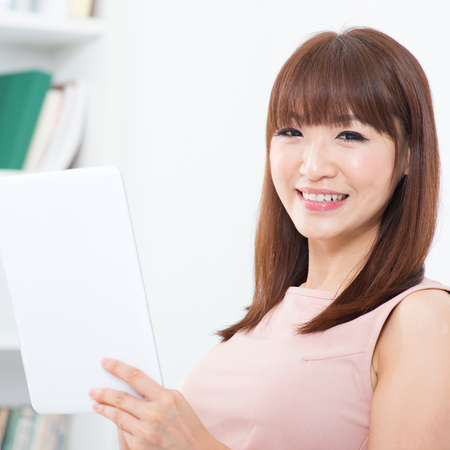 Portrait of attractive Asian girl using digital tab and smiling happily. Young woman indoors living lifestyle at home. photo