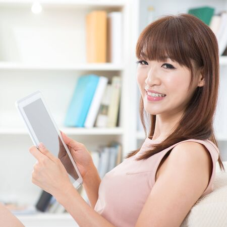 relaxing at home: Portrait of attractive Asian girl using digital pc tablet and smiling happily looking at camera. Young woman indoors living lifestyle at home. Stock Photo