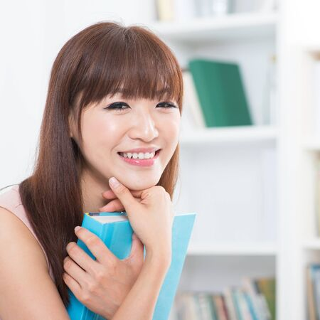 one room school house: Portrait of attractive Asian college girl with textbook. Young woman at school library. Stock Photo