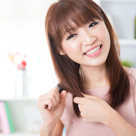 combing: Portrait of attractive Asian girl combing hair in the morning. Young woman indoors living lifestyle at home.