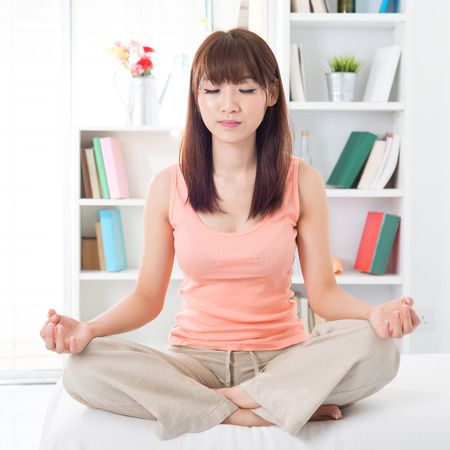 Portrait of calm Asian girl meditating in the morning. Young woman indoors living lifestyle at home. photo