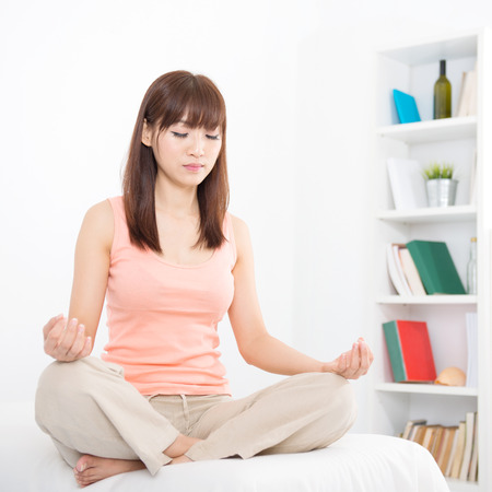 Portrait of calm Asian girl practicing yoga lotus position in the morning. Young woman indoors living lifestyle at home. photo