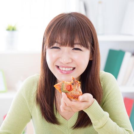 eten: Aziatische vrouw het eten van pizza thuis. Vrouw levend levensstijl binnenshuis. Stockfoto