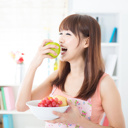 PRETTY WOMEN: Happy Asian housewife with apron eating green apple, holding bowl of fresh fruits. Young woman indoors living lifestyle at home.