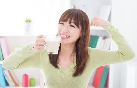soja: Retrato de la muchacha asi�tica feliz mostrando fuerte brazo mientras bebe la leche como desayuno. Mujer joven del estilo de vida en el interior que vive en casa. Foto de archivo