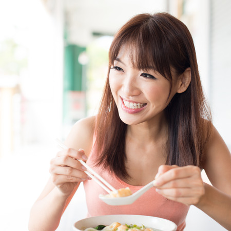 comida japonesa: Muchacha asiática que come fideos dumpling y hablando con un amigo en el restaurante chino. El estilo de vida de estar Mujer joven.