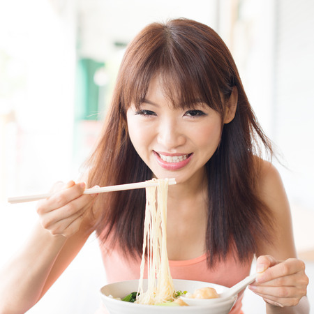 chinese noodle: Asian girl eating noodles at restaurant. Young woman living lifestyle.