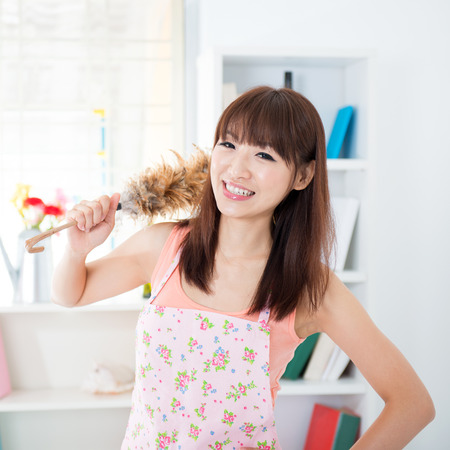 chinese lady: Happy Asian housewife with apron housekeeping, hand holding a duster and smiling. Young woman indoors living lifestyle at home.