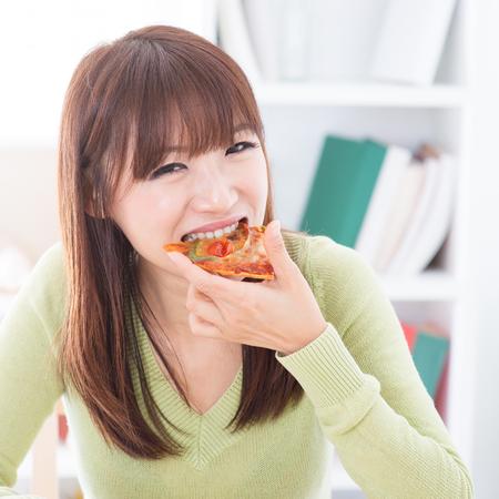 Asiatisches Mädchen, die Pizza essen zu Hause. Weiblich wohnhaft Lebensstil Innenbereich.