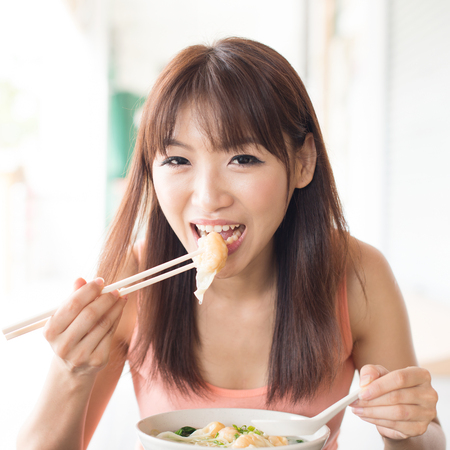 chinese lady: Asian girl eating delicious dumplings at Chinese restaurant. Young woman living lifestyle. Stock Photo