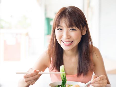 niñas chinas: Muchacha asiática que come los tallarines de verduras en el restaurante chino. El estilo de vida de estar Mujer joven.