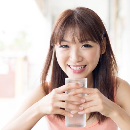 agua potable: Agua mineral feliz asiática niña bebiendo en el café al aire libre. El estilo de vida de estar Mujer joven. Foto de archivo