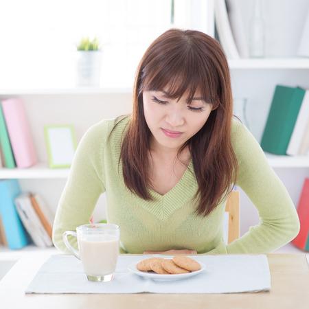 Femme tenant l'estomac et de la souffrance des maux d'estomac, tout en ayant le lait de vache et les cookies que le petit déjeuner, assis à manger les gens vivant table.Young intérieur mode de vie à la maison. Banque d'images