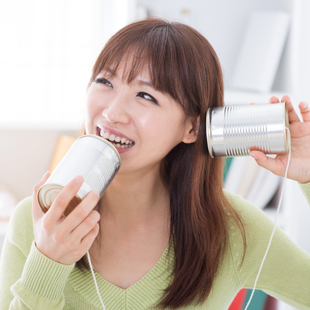 old asian: Asian girl using old technology, talk and listen to communication cans. Young woman indoors living lifestyle at home.