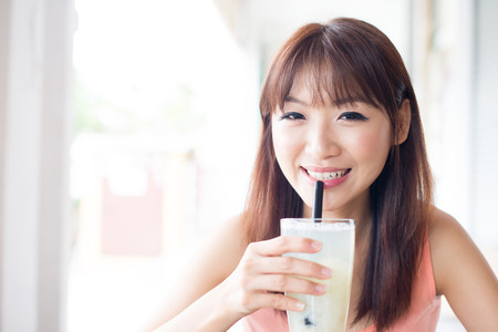 straws: Asian girl drinking a glass of beverage with straw in cafe. Young woman living lifestyle. Stock Photo