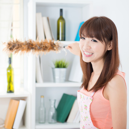 housecleaning: Happy Asian housewife with apron cleaning house, hand holding a duster and smiling. Young woman indoors living lifestyle at home.