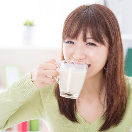 Portrait of happy Asian girl drinking milk as breakfast. Young woman indoors living lifestyle at home. Imagens