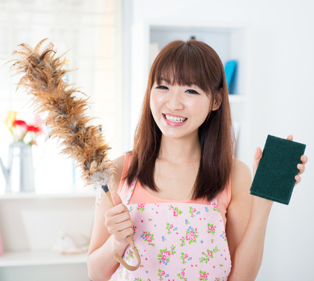 Happy Asian housewife with apron housecleaning, hand holding duster and cleaning sponge. Young woman indoors living lifestyle at home.