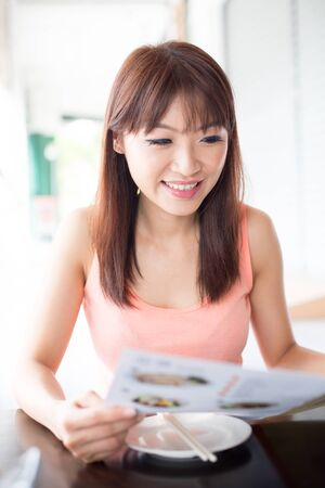 ordering: Asian girl looking at menu and ordering foods in restaurant. Young woman living lifestyle. Stock Photo