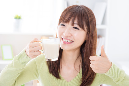 Portrait of happy Asian girl thumb up while drinking milk as breakfast. Young woman indoors living lifestyle at home. Archivio Fotografico