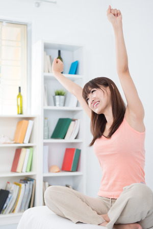 Portrait of Asian girl woke up and stretching arms in the morning. Young woman indoors living lifestyle at home. Stock Photo