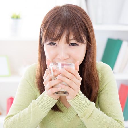 leche de soya: Retrato de feliz asiática leche de soja niña bebiendo como el desayuno. Mujer joven del estilo de vida en el interior que vive en casa.
