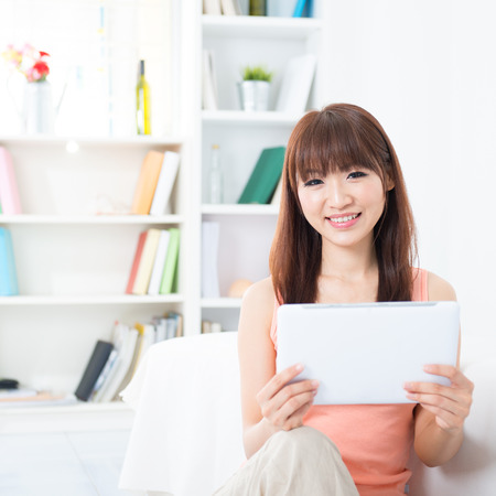 modern girl: Happy Asian girl using social media with tablet computer, social networks concept. Young woman indoors living lifestyle at home.