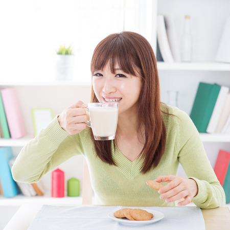 leche de soya: Retrato de la muchacha asiática feliz beber leche de soja y tener las cookies como desayuno. Mujer joven del estilo de vida en el interior que vive en casa.