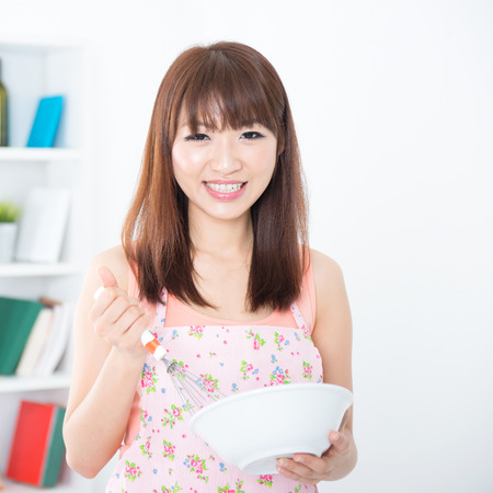Happy Asian housewife with apron preparing food, using manual egg mixer and bowl. Young woman indoors living lifestyle at home. photo