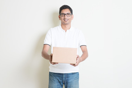 indian boy: Courier delivery service concept. Indian man received a brown box, standing on plain background with shadow. Asian handsome guy model.
